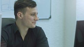 Oficinista que sonr?e y que mira la c?mara Hombre joven atractivo usando el ordenador en su lugar de trabajo almacen de metraje de vídeo