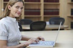 Oficinista que usa el ordenador portátil en oficina Fotografía de archivo