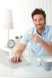 Oficinista sonriente en el escritorio con el teléfono handheld Fotos de archivo libres de regalías
