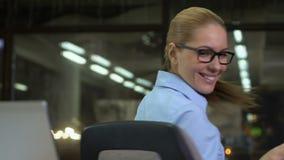Oficinista sonriente que da vuelta alrededor de la silla de la oficina, contrato acertado que disfruta almacen de metraje de vídeo