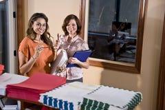 Oficinistas de sexo femenino que se colocan en sala de correo Foto de archivo libre de regalías