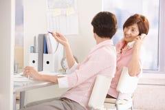 Oficinistas de sexo femenino que se sientan en el escritorio Imágenes de archivo libres de regalías