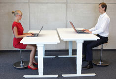 Oficinistas en la posición sentada correcta en los escritorios con los ordenadores portátiles foto de archivo libre de regalías
