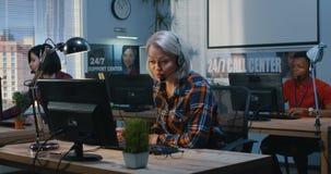 Oficinistas en sus escritorios en un centro de ayuda