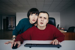 Oficinistas hermosos jovenes sorprendidos de la gente emocionalmente que miran una pantalla de ordenador La situación en la ofici Foto de archivo
