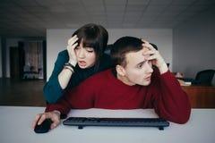 Oficinistas jovenes frustrados cerca del ordenador Gente joven hermosa emocional en el lugar de trabajo Imagen de archivo