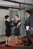 Oficinistas que sacuden las manos en la puerta de la sala de reunión Fotografía de archivo libre de regalías