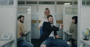 Oficinistas que se divierten en el tiempo de la rotura, la mujer de negocios rubia hermosa y su colega jugando con una silla almacen de video