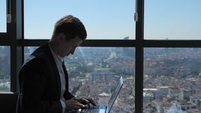 Ofiice worker in suit is typing on laptop sitting near the window with panoramic city view. Businessman is working on his laptop in office writing a message. He stock footage