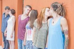 Ofpeople medio del grupo que se besa y que se coloca cerca de fondo rojo de la pared Foto de archivo libre de regalías