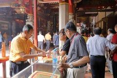 Ofrendas de la compra de los creyentes tales como incienso y papel del ídolo chino en el templo de Xiamen Tzu Chi Foto de archivo