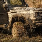 Ofroad for hard man. Car after offroad racing on sunny day. Wheel, bonnet, mirror and door covered with mud. Fragment of car with autumn nature on background royalty free stock images