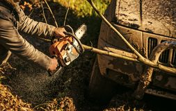 Ofroad for hard man. Male hands hold chainsaw and car covered with mud. On sunny nature background. Sawing branch in front of bumper and light of SUV Royalty Free Stock Images