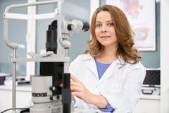 Oftalmólogo de sexo femenino que presenta con la máquina de la prueba del ojo fotos de archivo