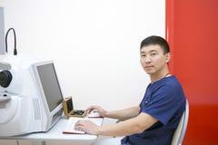 Oftalmólogo de sexo masculino del doctor en el lugar de trabajo foto de archivo libre de regalías