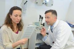Oftalmólogo que pide que el paciente lea la página fotos de archivo