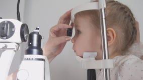 Oftalmología del niño - optometrista que comprueba la visión del ` s del pequeño niño imagen de archivo libre de regalías