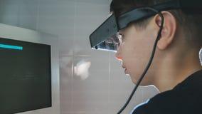 Oftalmología - el muchacho del niño comprueba ojos con los vidrios y el monitor estéreos Foto de archivo