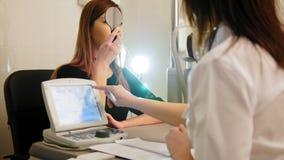 Oftalmologia medica, salute, concetto - bella visione dei controlli della ragazza in un oftalmologo con un occhio chiuso archivi video