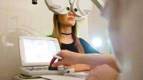 Oftalmologie - het concept van de ogenkliniek - optometrist en patiënt die examenvisie doen door moderne elektronische technologi stock videobeelden