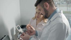 Oftalmologista alegres que selecionam as lentes experimentais filme