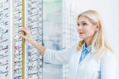 oftalmologista profissional que está no sistema ótico com vidros fotos de stock