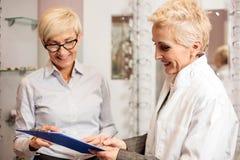 Oftalmologo femminile maturo che redige i dati del paziente ad una lavagna per appunti, funzionante in un deposito ottico fotografia stock