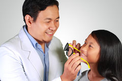 Oftalmologo Giving Eyeglasses ad una ragazza immagini stock libere da diritti
