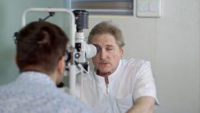 Oftalmoloog en jonge mens die zicht in kliniek controleren stock afbeelding