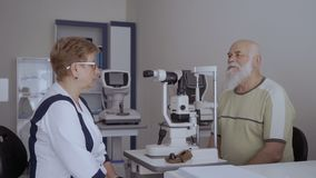 Oftalmoloogbespreking met oude patiënt na het controleren van zijn visie stock videobeelden