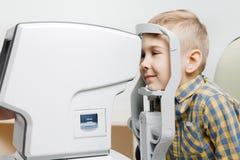 Oftalmoloogvrouw arts die visie van weinig kind in kliniek onderzoeken royalty-vrije stock afbeelding