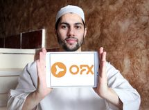 OFX financial services company logo. Logo of OFX company on samsung tablet holded by arab muslim man. OFX is an Australian online foreign exchange and payments royalty free stock photo