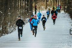 Ogólnego planu bieg przez śnieżnej Parkowej alei grupy mężczyzna atlety Zdjęcia Royalty Free
