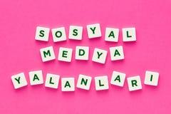 Ogólnospołeczni środków kłamstwa pisać z listami na różowym tle zdjęcia royalty free