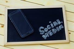 Ogólnospołeczny medialny pojęcie z smartphone i słowa OGÓLNOSPOŁECZNYM środkami pisać na blackboard Obraz Royalty Free