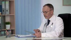 Ogólny lekarz praktykujący utrzymuje elektroniczne książeczki zdrowia, współczesna medycyna zdjęcie stock