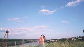 Ogólny plan, piękny mężczyzna i kobieta, całujemy w centrum rama, most, rzeka, drzewa, trawa, domy przeciw zbiory wideo