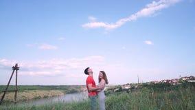 Ogólny plan, przystojny mężczyzna i kobieta po buziaka, śmiamy się wokoło i błaź się w centrum rama most, rzeka, drzewa zbiory