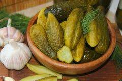 Ogórki w drewnianym pucharze, pikantność dla bejcować i słojach kiszeni ogórki na stole, fotografia stock