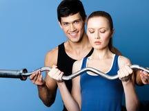 Ogłoszenie towarzyskie trener pokazuje kobiecie poprawnego ćwiczenia spełnianie zdjęcie stock