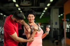 Ogłoszenie towarzyskie trener z w średnim wieku kobietą w gym obrazy stock