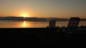 Ogenblik die van zon achter berg en een leeg strand toenemen stock videobeelden