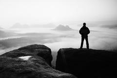 Ogenblik van eenzaamheid Mens op de rotsimperiums en horloge over de nevelige en mistige ochtendvallei aan Zon royalty-vrije stock foto's