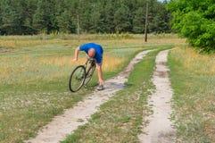 Ogenblik van het vallen weg van de rijpe mens op een oude fiets royalty-vrije stock afbeelding