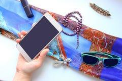 Oggetti di vita femminile su una tavola bianca, telefono, fibula, sciarpa di colore Fotografia Stock
