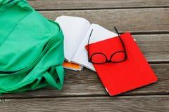 Oggetti per la allievo-compressa, taccuino, occhiali da sole, zaino su fondo vuoto Immagine Stock