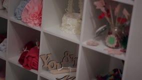 Oggetti per la decorazione delle feste e delle nozze Scaffale bianco con gli elementi decorativi del panno stock footage
