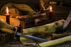 Oggetti sul tema marino, libri e candele brucianti, vecchi documenti e un pugnale di marinaio, una bugia della mappa su un fondo  immagine stock