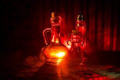 Oggetto d'antiquariato e bottiglia di vetro d'annata su fondo nebbioso scuro con luce Veleno o concetto del liquido di magia fotografie stock libere da diritti