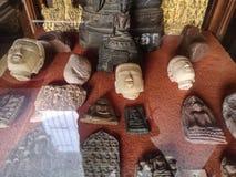 Oggetto d'antiquariato e raccolta amuleti e delle teste santi antichi di Buddha dietro la finestra fotografia stock